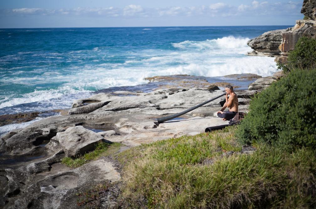 A man plays the Digeridoo on the rocks